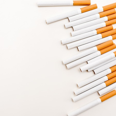 Cigarette with orange filter on the white surface. The view from the top. Imagens