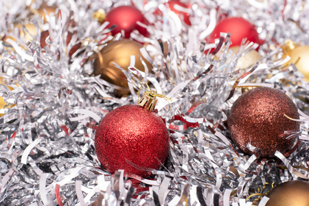 Beautiful Christmas toys of gold, brown and red flowers on the background of silver tinsel Archivio Fotografico