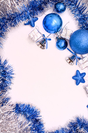 Flat lay consisting of blue Christmas toys and silver tinsel