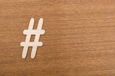 Hashtag sign made of wooden material on wooden background. Top view