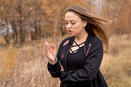 Young beautiful woman with cigarette in black clothes on autumn day