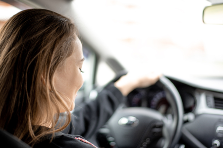 Girl driving a car . Removed from the back seat. The machine panel is blurred. Stock Photo