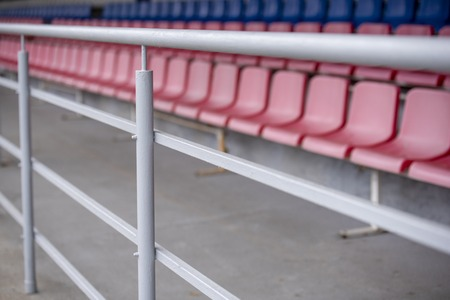 Metal fence stands with empty plastic seats to protect fans 版權商用圖片