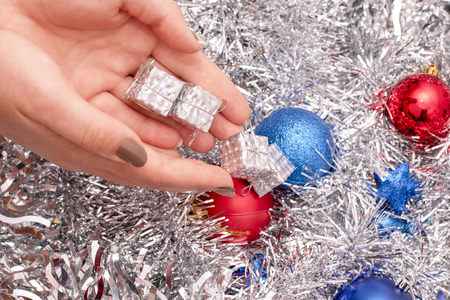 Small silver gift boxes in woman's hand on the background of tinsel and Christmas toys