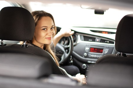 Belle jeune femme assise dans la voiture au volant et regardant en arrière et souriant