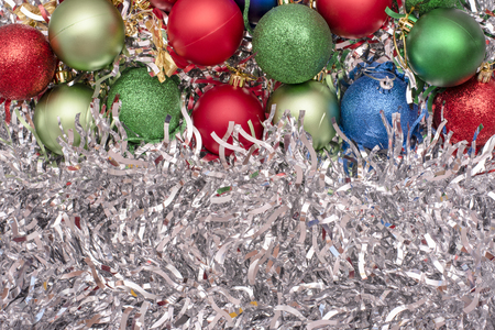 Beautiful Christmas toys of green, blue and red colors on the background of silver tinsel Archivio Fotografico