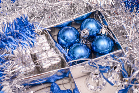 Christmas toys consisting of blue stars, blue Christmas balls, silver bells and gift boxes in box between the silver tinsel