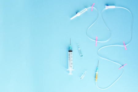 Medical disposable syringe, ampoules and dropper tube on blue background . The view from the top. Copy space