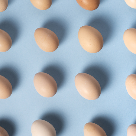 Brown eggs set in a straight line on a blue background. Top view Imagens