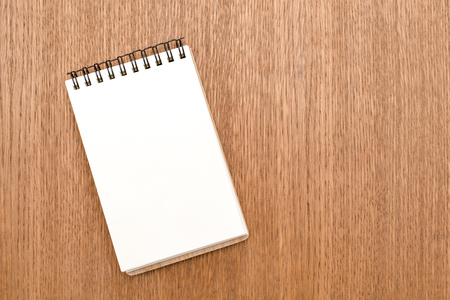 Blank notebook with spiral for the application of labels on wooden background. Top view Imagens
