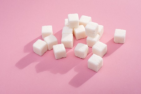 Sugar cubic sugar on a pink background. Shot in the Studio