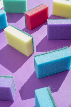 Multi-colored rectangular sponges for washing dishes on a purple background Archivio Fotografico