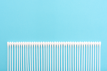 White cotton buds on a blue background lie in a straight line at the bottom of the photo. Copy space