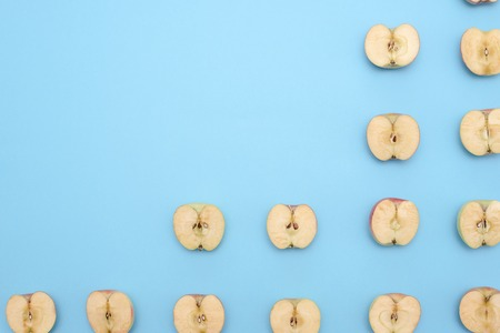 Background of cut in half apples on blue background. Top view Stock Photo