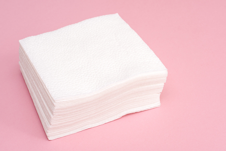 Stack of white square paper napkins on pink background Stock Photo - 122269256