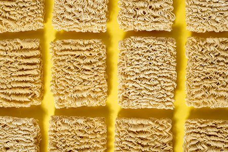 Instant noodles on a yellow background are arranged in a row