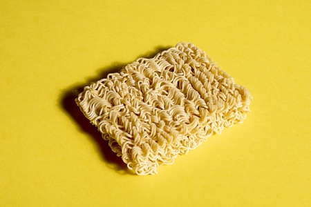 Instant noodles on yellow background . Shooting in the Studio.