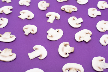Sliced mushrooms on purple background. Top view