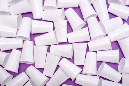 Disposable plastic white empty cups on purple background Stockfoto