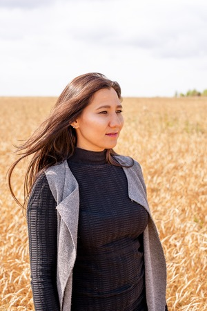 A beautiful girl stands in a rye field and looks into the distance