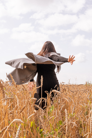 A girl in a gray vest runs rye field. Rear view. Autumn day Stockfoto
