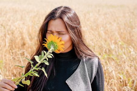 Brünettes Mädchen steht auf einem Roggenfeld und schnuppert an einer Sonnenblume
