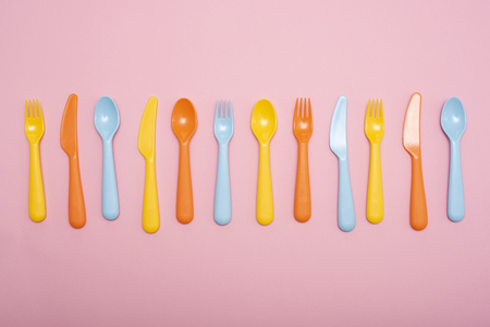 Colorful dining set on pink background . Top view. 스톡 콘텐츠
