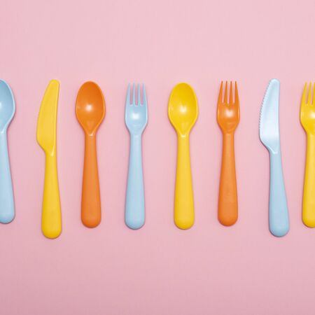 Colorful tableware : spoon, knife, fork in range on pink background. Plastic. 写真素材