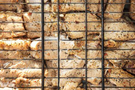 Pork divided into pieces preparing on the grid. Zdjęcie Seryjne