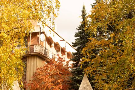 The building of the sanatorium with balconies between the trees in the autumn bright Sunny day