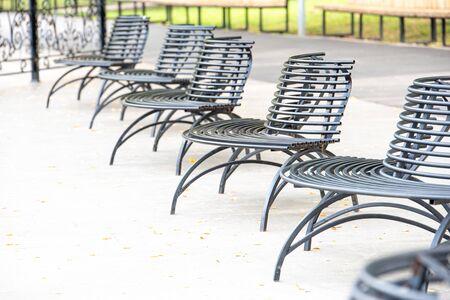 Iron black bench in park in autumn day
