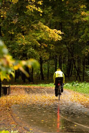 Biking in colorful park during rain with autumn foliage Banque d'images