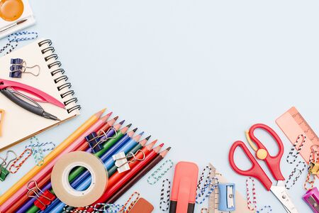 Education or back to school concept. Top view of colorful school supplies with color pencils, ruler, eraser,clips on blue background. Flat lay.