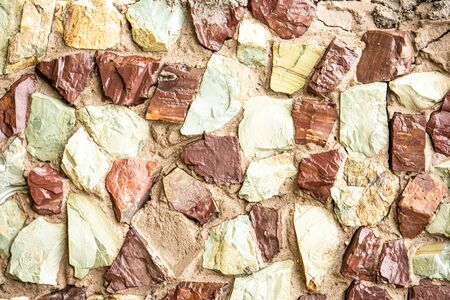 Stone wall of natural stones of red green yellow colors . Background.