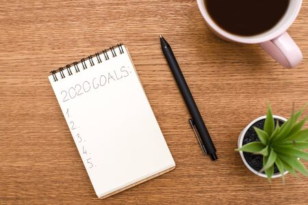 Top view 2020 goals list with notebook, cup of coffee on wooden desk Banque d'images