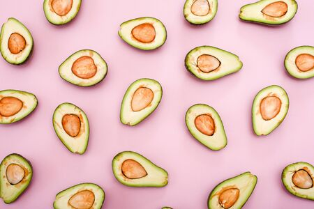 Avocado natural color and condition divided in half on a pink background. Flat lay