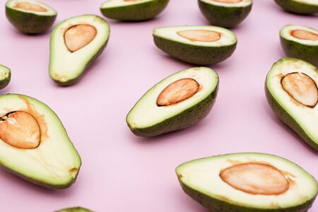 Avocado natural color and condition divided in half on a pink background. Close up