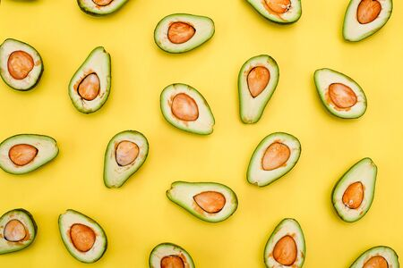 Avocado natural color and condition divided in half on a yellow background. Flat lay Banque d'images