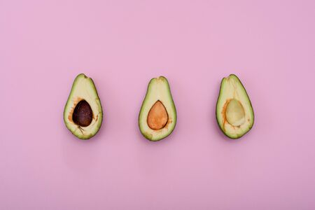 Avocado natural color and condition divided in half on a pink background. With and without bones. Three.