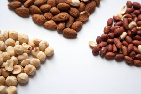 Hazelnuts, almonds and peanuts on white background closeup