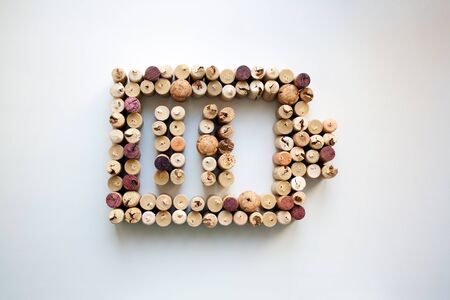 Wine corks battery charge level abstract composition isolated on white from a high angle view Standard-Bild