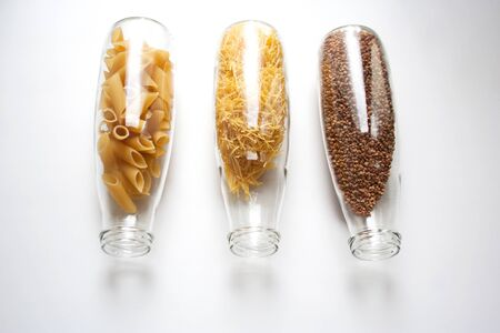 Penne rigate, egg pasta and buckwheat stored in a transparent glass bottles isolated on white background