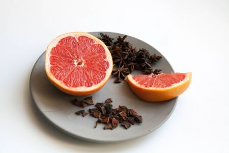 Juicy sliced grapefruit and heap of star anise spices isolated on grey concrete plate