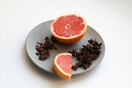 Fresh grapefruit slices and heap of star anise spices isolated on grey concrete plate 写真素材