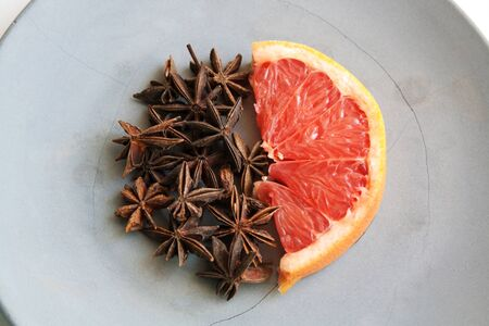 Grapefruit slice and star anise round composition on grey concrete plate isolated on white background close up 写真素材