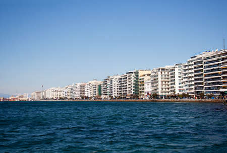 Waterfront buildings facades along Thessaloniki embankment busy with shops and cafes under clear spring sky