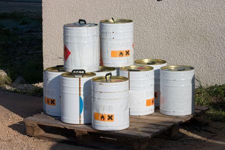 Envases del metal de productos químicos industriales que se sientan fuera de una planta.