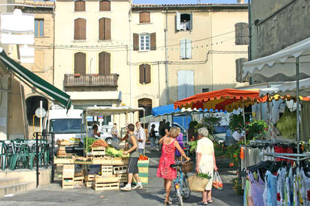 An image of French village life on market day showing people, vegetables, clothing. photo