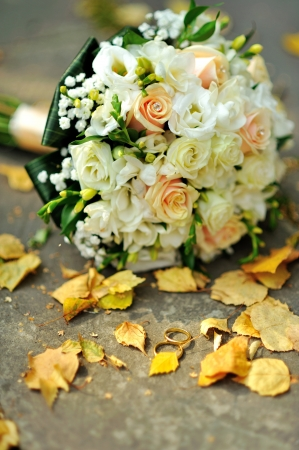 bridal bouquet and golden wedding rings outside, sunny autumn day photo