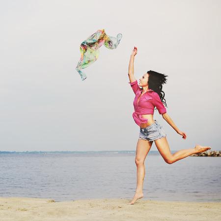 若い女性はビーチでリラックスできる自由を感じる